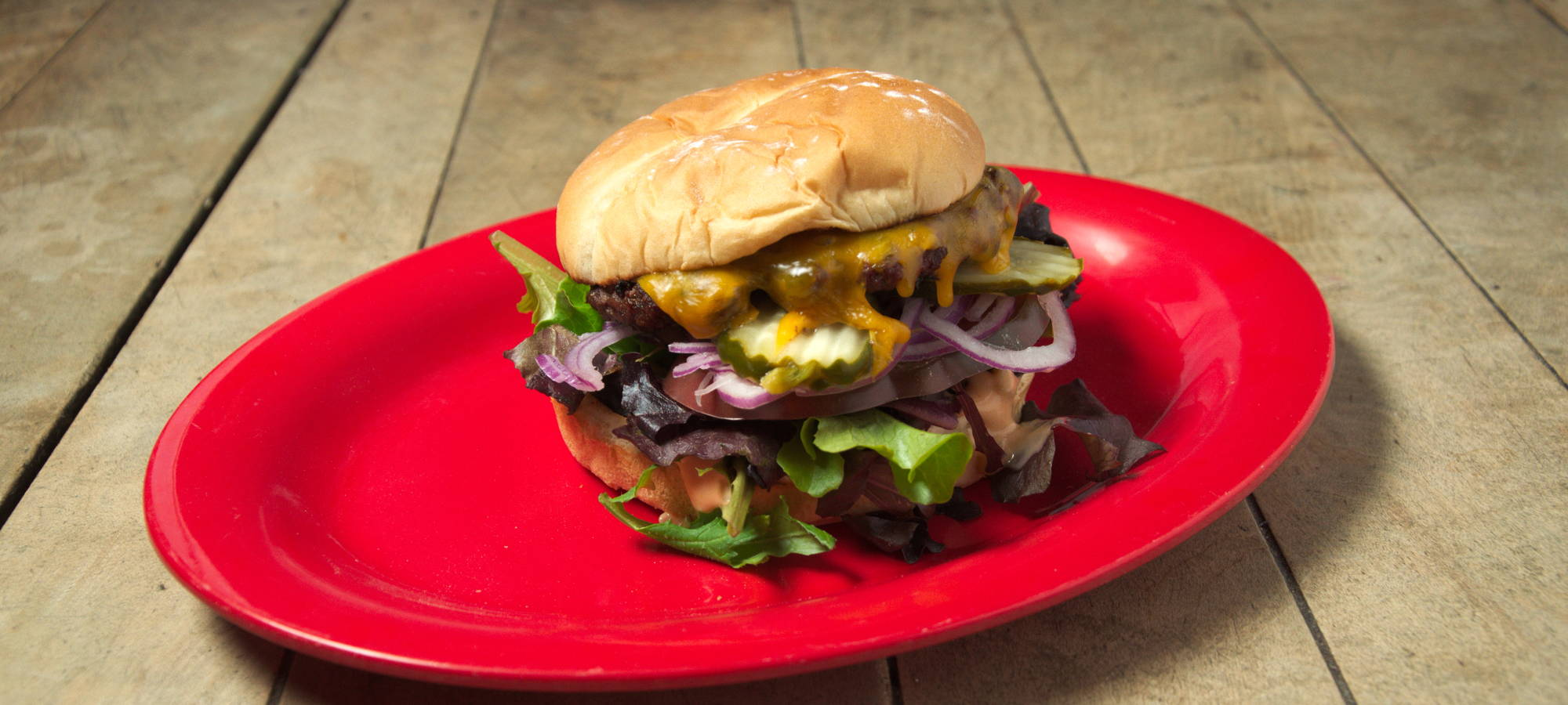 A cheeseburger on a plate set on a wooden tabletop