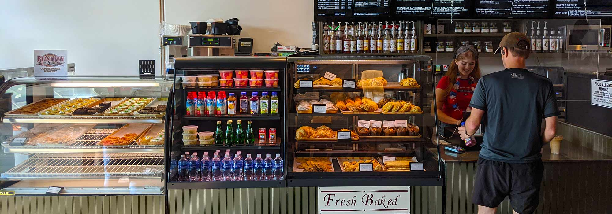 Photo of pastry cases, grab and go items, and a barista serving a customer at the front counter.