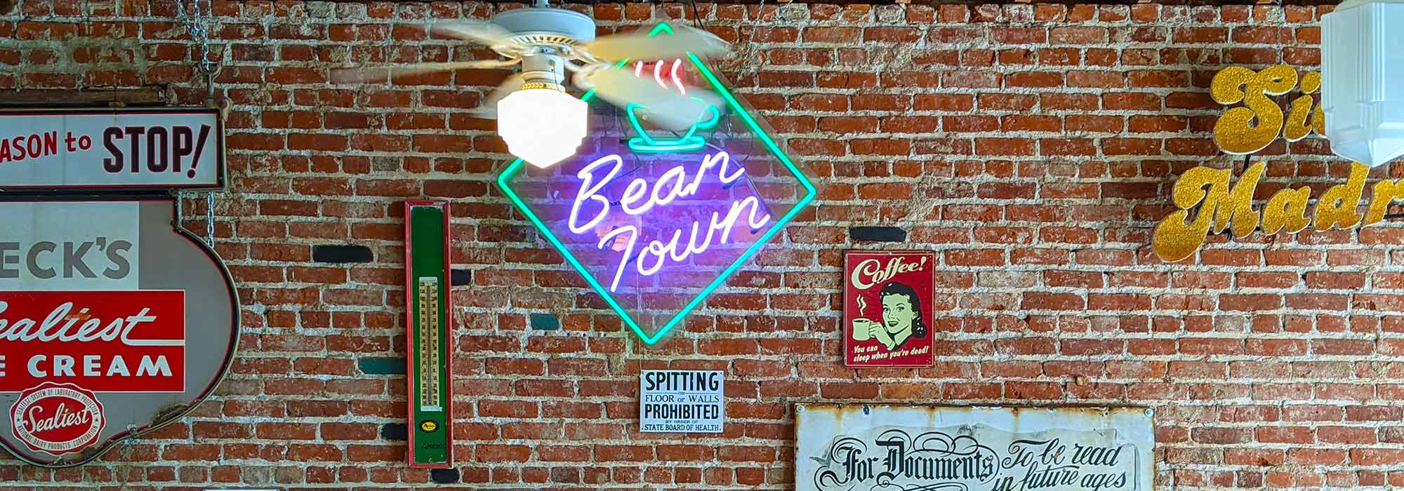 Photograph of a brick wall containing various decorations, including a neon sign that reads 'Bean Town'. A moving ceiling fan hangs in the foreground.