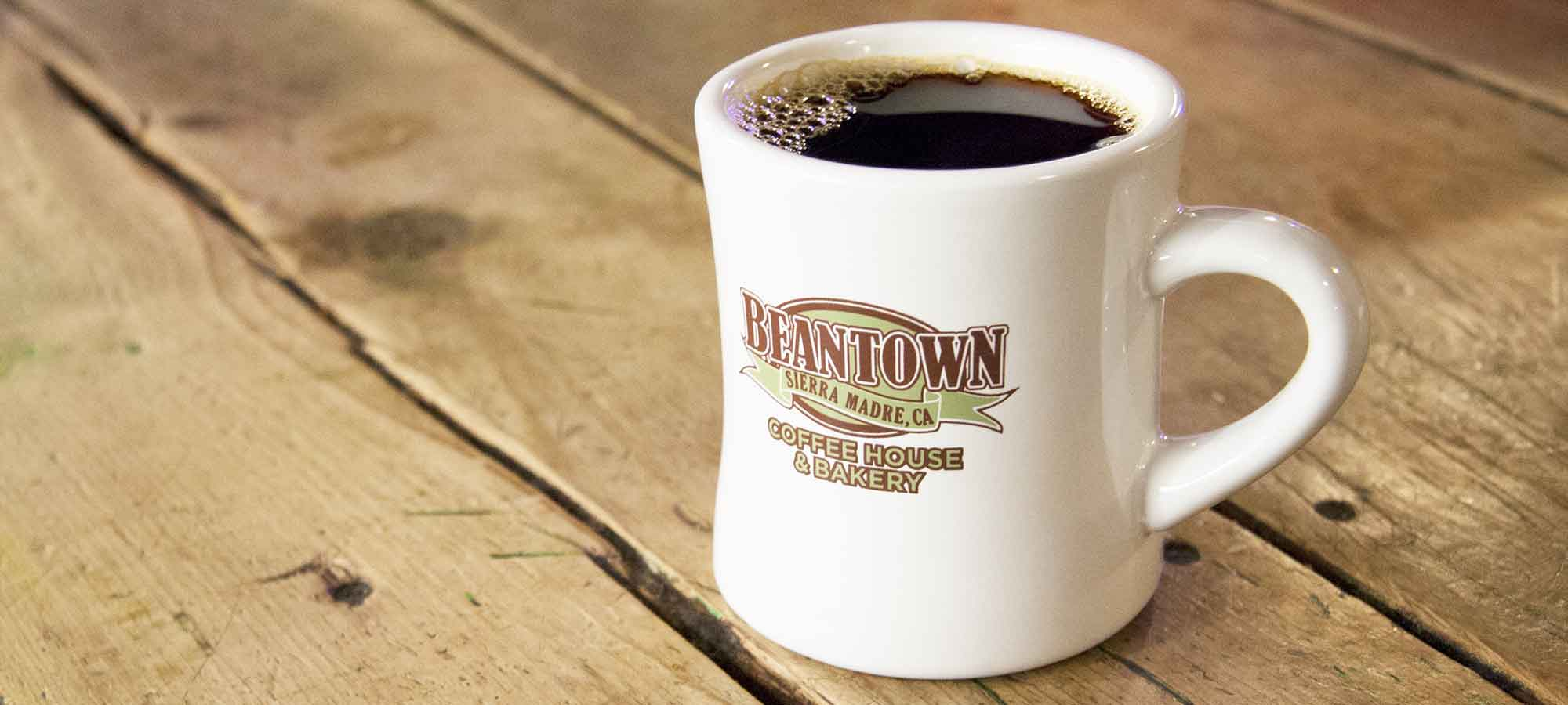 Bean Town ceramic mug filled with coffee on a wooden table